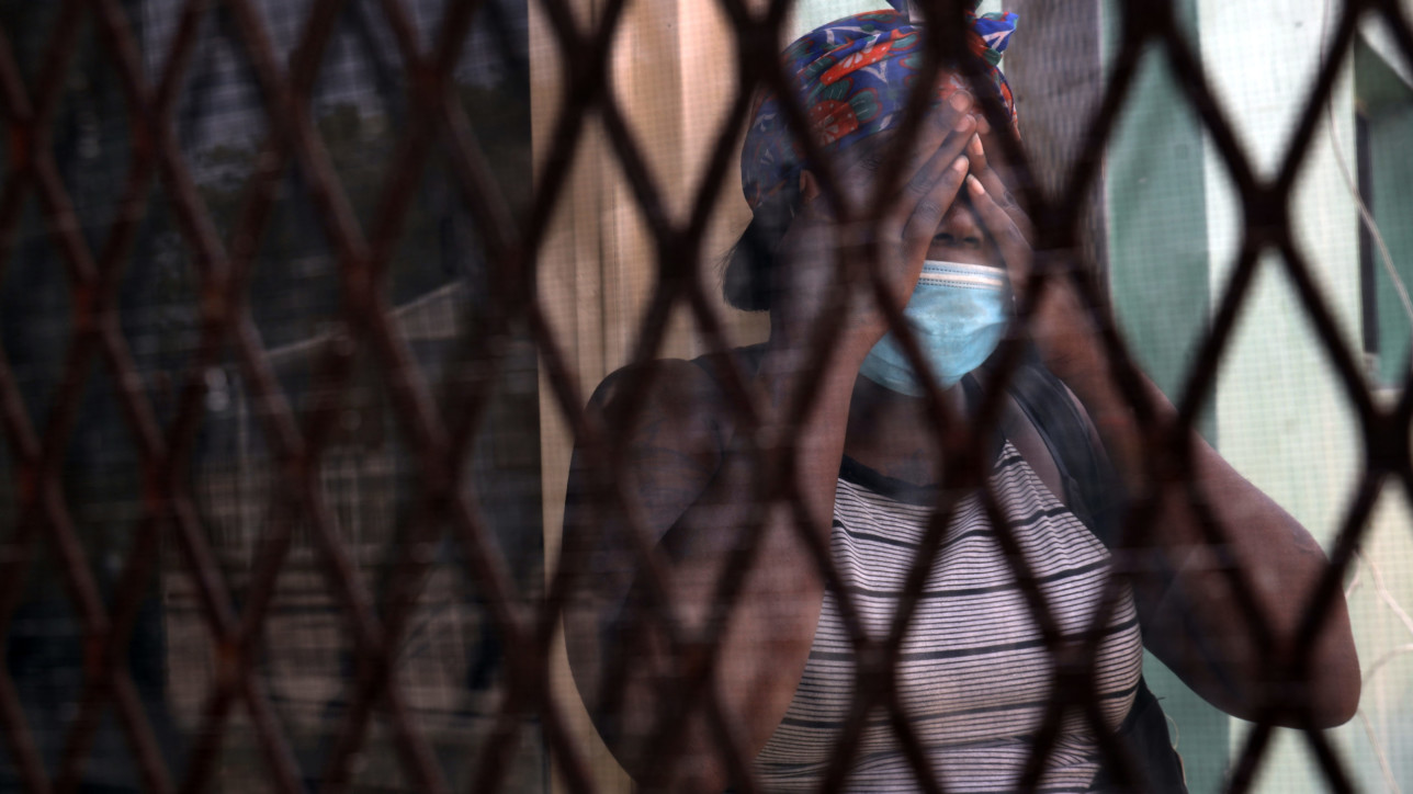A resident of Liberty Square housing projects stand at her mother's kitchen door.  Like many residents, she and mother are following COVID-19 health policies and social distancing guidelines by wearing masks when venturing outdoor and sheltering-in-place as the nation tries to flatten the curve of the rate of infection of the COVID-19 pandemic.